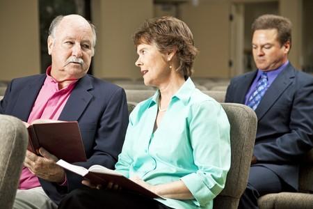Mündig paar sitzen in der Kirche, die Gesangbücher halten.