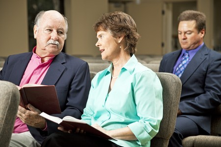 Mature couple sitting in church holding hymnals.   Archivio Fotografico