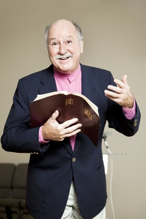 preaching: Minister holding a bible and preaching a positive, inspiring sermon.   Stock Photo