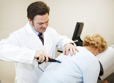 Chiropractor uses the latest computer technology to diagnose and treat a patient.   photo