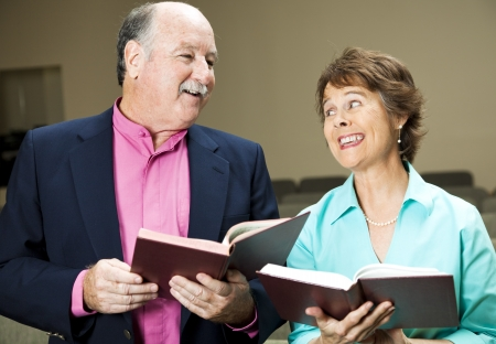 Husband and wife in church, singing hymns.   photo