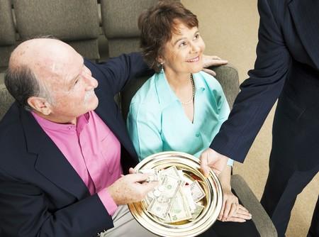 acomodador: Colocar el dinero en la placa de la colecci�n de miembros de la Iglesia.  Foto de archivo