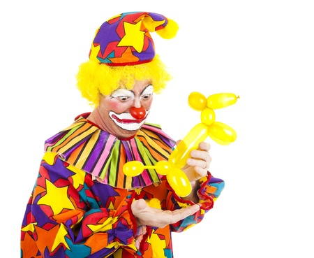disgusted: Humorous picture of a clown looking disgusted as a balloon animal poops in his hand.   Stock Photo