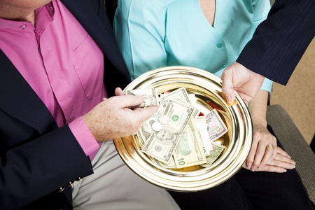 religious service: Church receives donations by passing the collection plate.   Stock Photo