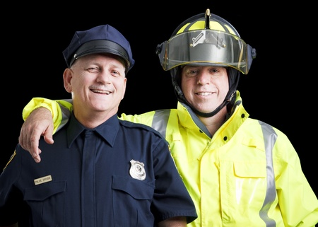 Portrait of happy, smiling police officer and fire fighter on black background.   photo