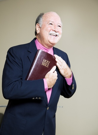 Happy minister holding the Bible and preaching a message of love.   Stock Photo
