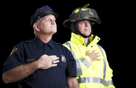 Police officer and fire fighter with their hands over their hearts as they say the Pledge of Allegiance.   photo