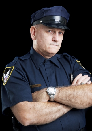 watchman: Portrait of a serious police officer with arms folded, against a black background.