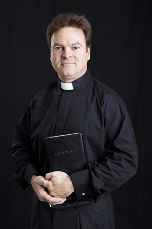 devoted: Portrait of a catholic priest holding the bible.  Black background.   Stock Photo