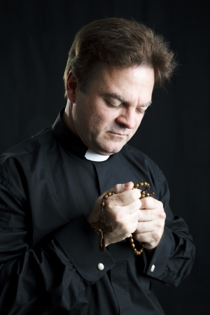 Priest holding his rosary and praying.  Black background and dramatic lighting.   版權商用圖片