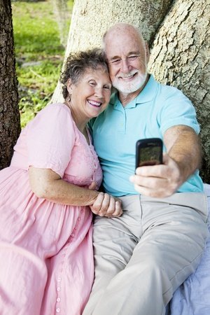 Senior couple e-mailing a picture of themselves to their kids, using a cellphone.   photo
