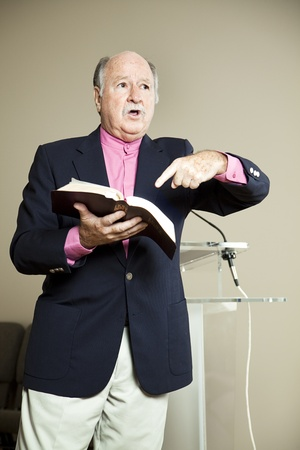 Minister preaching and pointing to the Bible.
