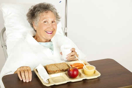 Senior hospital patient eating her lunch on a tray.