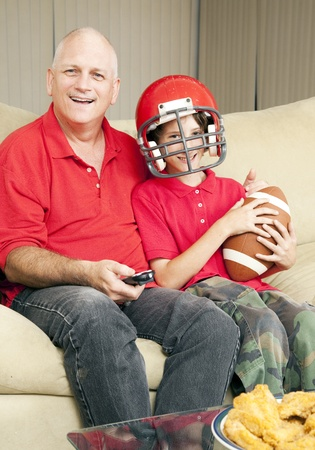 Father and his son watching a football game together.   photo