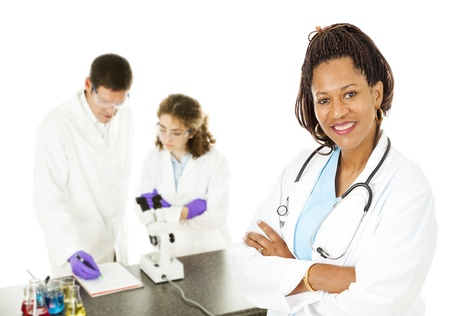 African-american female doctor with lab techs in background.  Isolated on white.   photo