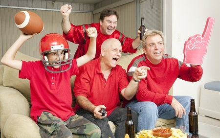 red sofa: Excited football fans watching their team score a touchdown.