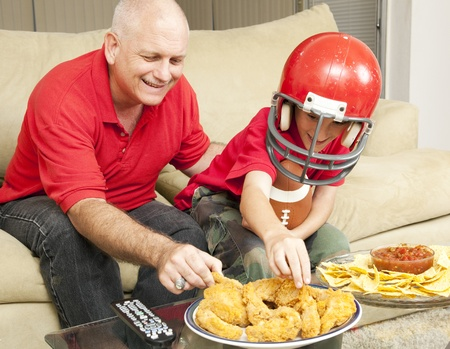 sport fan: Father and son watching football together and eating snacks.