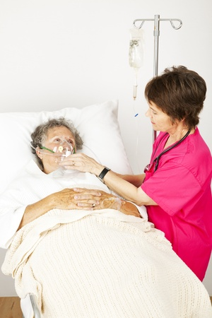 Senior woman in the hospital with lung disease, getting oxygen from a nurse.   photo