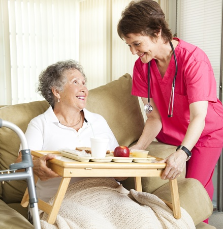 Retired senior woman in nursing home gets lunch from a caring nurse.   Standard-Bild