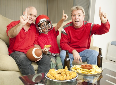 A little boy watching the super bowl with his father and uncle.