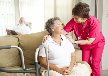 Senior woman in a nursing home, with a caring nurse.   photo
