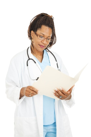 Beautiful african-american doctor reading a patients medical chart.  Isolated on white.   photo