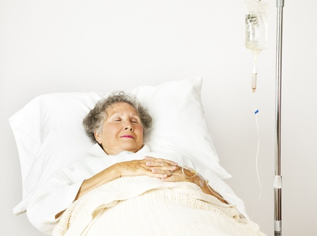 Senior woman sleeping in a hospital bed.   photo
