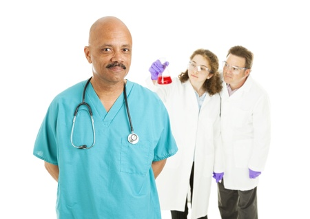 Handsome African-american surgeon with lab techs in background.    Isolated on white.   photo