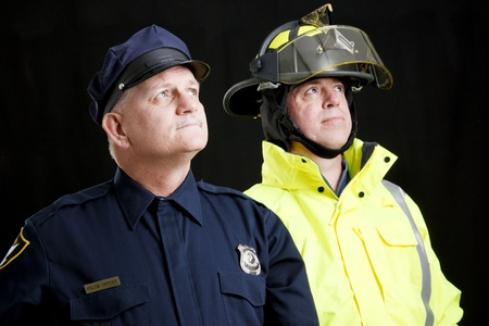 safety officer: Reverent looking policeman and fireman photographed in front of a black background.