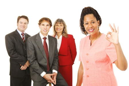 Portrait of african-american female business woman with her team, giving the Okay sign.  Isolated on white. photo