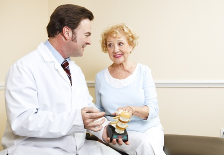 Chiropractor uses a model of the human spine to explain treatment to a new patient. Stock Photo - 8627727