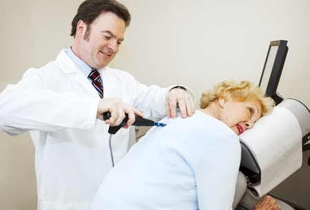 Friendly, smiling chiropractor adjusting a senior womans back.   photo