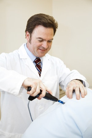 back ache: Chiropractor using a digital tool to adjust a patients back.   Stock Photo