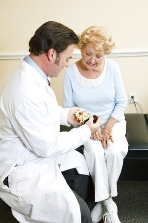 Chiropractor with a senior patient, looking at a model of the human spine.   Stock Photo - 8627751