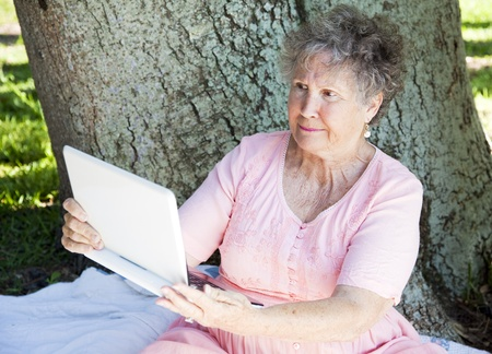 Senior woman trying to use a netbook computer and getting frustrated. photo