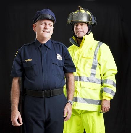 safety officer: Police officer and firefighter photographed together over a black background.