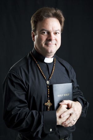 predicador: Retrato de un sacerdote con un Rosario y una Biblia.  Iluminaci�n dram�tica sobre fondo negro.   Foto de archivo