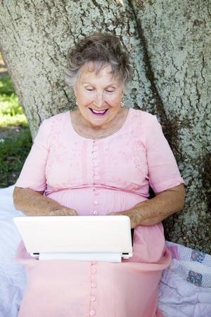 netbook: Senior woman enjoys using her netbook computer outdoors.   Stock Photo