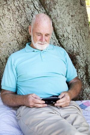 Senior man texting on his smart phone.   photo