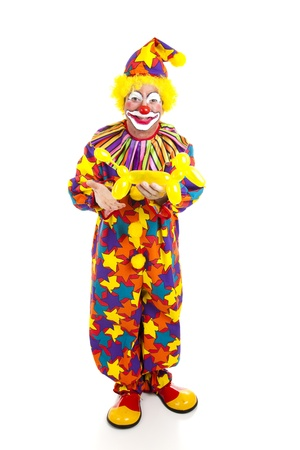 performers: Full body isolated view of a birthday clown holding a balloon animal.  Stock Photo