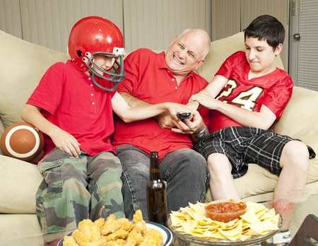 food fight: American football fans- father and sons - fighting for the television remote control.   Stock Photo