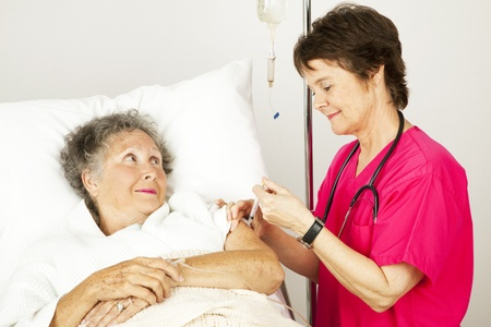 Hospital nurse giving an elderly female patient an injection in her arm.   photo