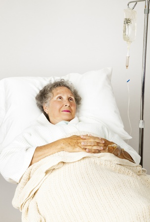 hospice: Lonely senior woman in the hospital bed, hooked up to an IV.
