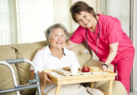 work from home: Friendly nurse brings a mean to an elderly shut-in.  Could also be lunch time at the nursing home.   Stock Photo