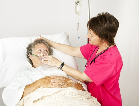 Hospital nurse helps a senior woman breath through an oxygen mask.   photo