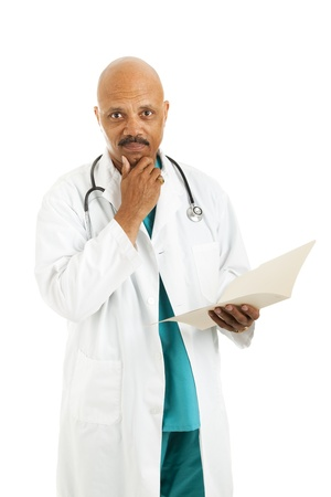 considers: Serious african-american doctor considers treatment options while reviewing a patients medical chart.  Isolated on white.