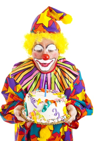 Funny clown blows out a candle on the birthday cake.  Isolated on white.  photo