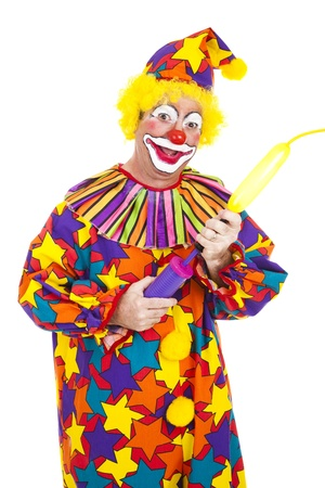 Funny birthday clown blows up a balloon to twist into an animal shape.  Isolated. photo