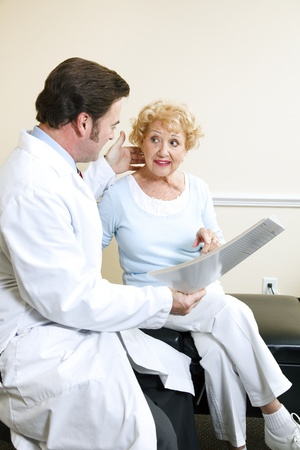 Chiropractic doctor and his elderly patient discussing her neck symptoms. Stock Photo - 8728042