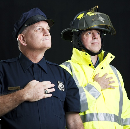 allegiance: Policeman and fireman saying the pledge of allegiance.  Photographed on black background.